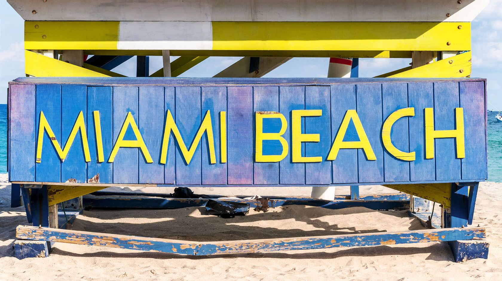 A Yellow And Blue Sign Sitting On Top Of A Sandy Beach